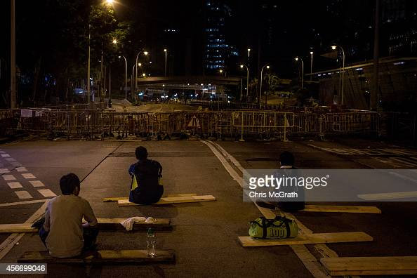 Prodemocracy protesters guard a perimeter barricade in the early hours of Monday morning outside the Hong Kong Government complex on October 6 2014...