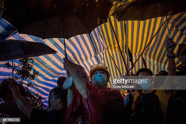 Prodemocracy protesters hold umbrellas up to support a tent during heavy rain on Nathan Road in Mong Kok on October 22 2014 in Hong Kong Police have...