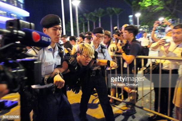 A prodemocracy protesters is removed by police officers from the golden bauhinia statue ahead of the 20th anniversary of Hong Kong's handover to...
