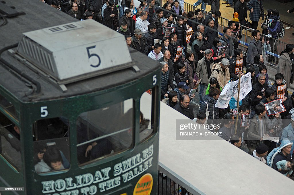 Pro-democracy protesters (R) shuffle past a tram (L) stuck in traffic as thousands take to the streets calling for new Hong Kong Chief Executive Leung Chun-ying to step down in Hong Kong on January 1, 2013. Organisers have said they expected 50,000 people to join the New Year's Day march against Leung Chun-ying, while pro-government groups staged separate and smaller rallies in support of the Beijing-backed chief executive.