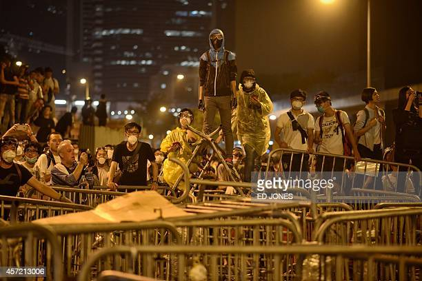 Prodemocracy protesters wait behind a barricade for approaching police outside the Legislative Council building in the Admiralty district of Hong...