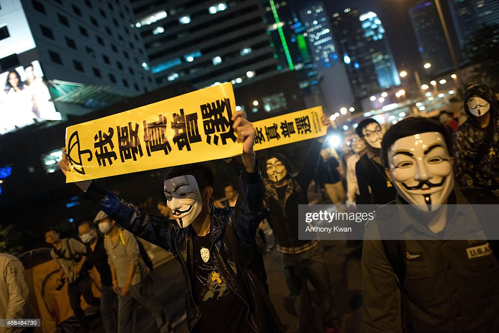 Pro-democracy protesters wear Guy Fawkes mask as they hold banners and shout slogans on a street near Hong Kong Government Complex in Admiralty district on November 5, 2014 in Hong Kong. Pro-democracy protesters staged a rally on Guy Fawkes day.