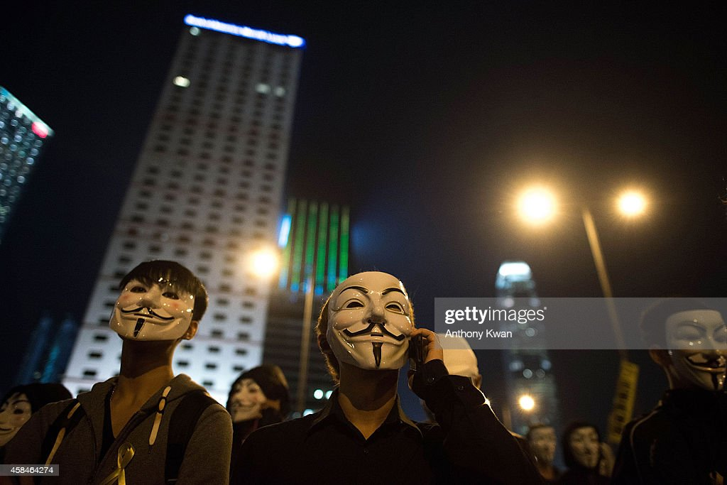 Pro-democracy protesters wear Guy Fawkes mask as they march on a street near Hong Kong Government Complex in Admiralty district on November 5, 2014 in Hong Kong. Pro-democracy protesters staged a rally on Guy Fawkes day.