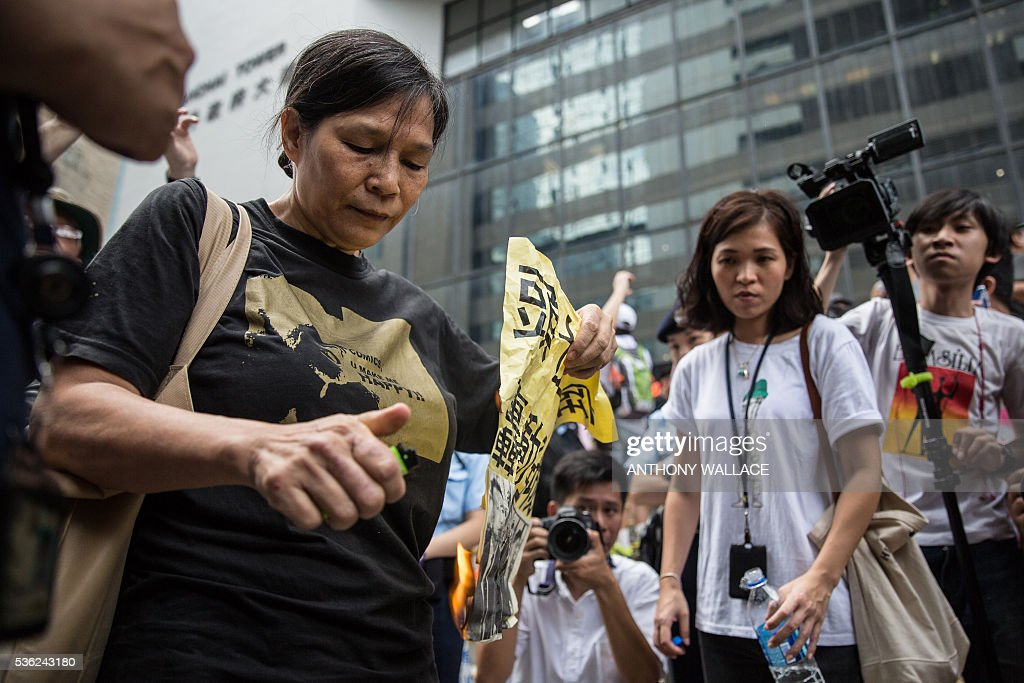 A pro-democracy protestor (L) sets fire to a poster, showing photos of members of the police who allegedly beat activist Ken Tsang during the 2014 pro-democracy protests, shortly after they arrived outside the District Court in Hong Kong on June 1, 2016. Seven Hong Kong police officers appeared in court on June 1 over the beating of a pro-democracy protester during mass rallies in 2014, an incident which was captured on film and beamed around the world. / AFP / ANTHONY