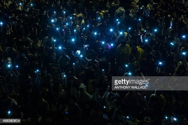 Prodemocracy protestors hold up their mobile phones after heavy rain in Hong Kong on September 30 2014 Hong Kong has been plunged into the worst...