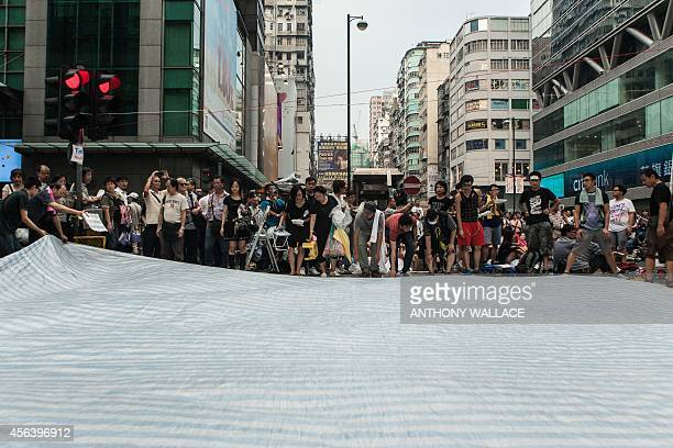 Prodemocracy protestors lay down a tarpaulin after rain in Hong Kong on September 30 2014 Hong Kong has been plunged into the worst political crisis...
