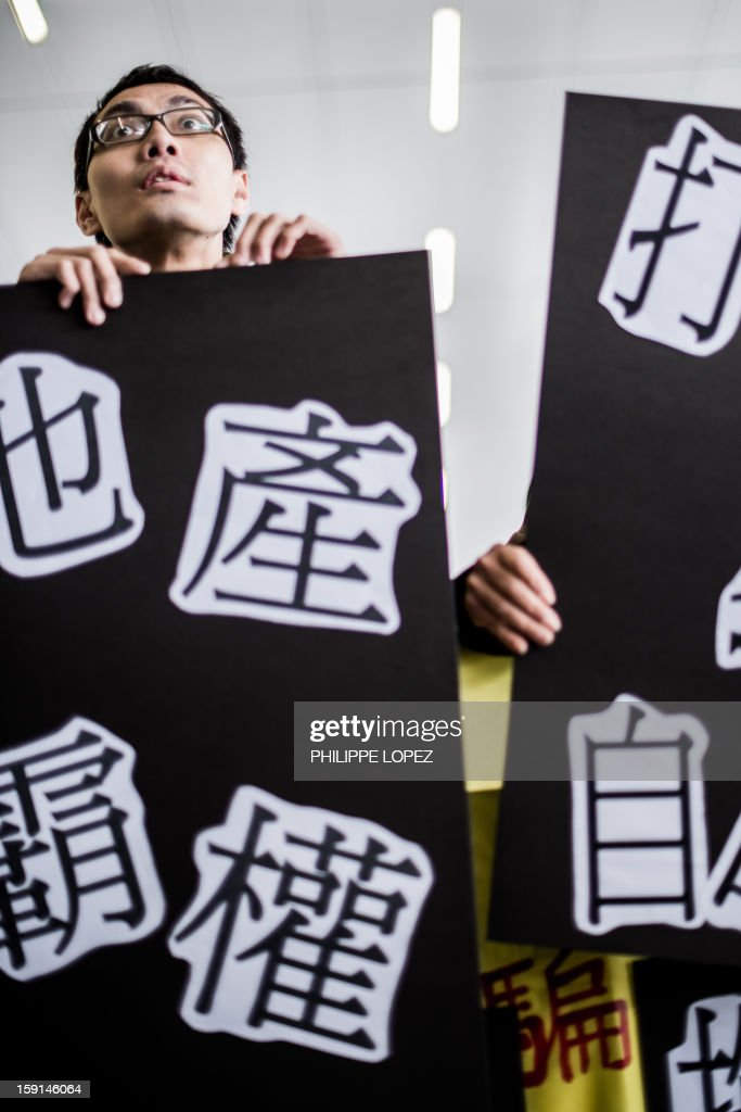 A pro-democracy supporter holding a placard looks towards demonstrators (not pictured) shouting slogans in support of Hong Kong Chief Executive Leung Chun-ying during a protest in Hong Kong on January 9, 2013. Pro-democracy lawmakers were expected to table an impeachment motion on January 9 against chief executive Leung Chun-ying, demanding him to quit over a housing scandal. AFP PHOTO / Philippe Lopez