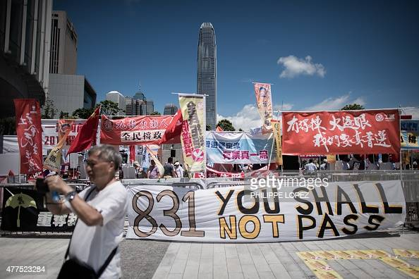 A prodemocracy supporter takes pictures after a vote outside the city's legislature in Hong Kong on June 18 2015 Hong Kong lawmakers rejected a...