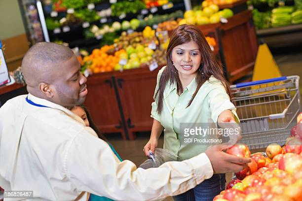 Produce worker helping customer at grocery store