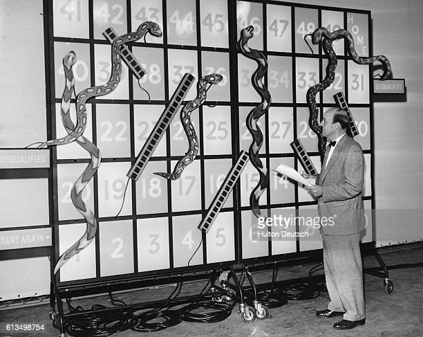 Producer Bill Perry stands at the game board for the new quiz show Snakes and Ladders