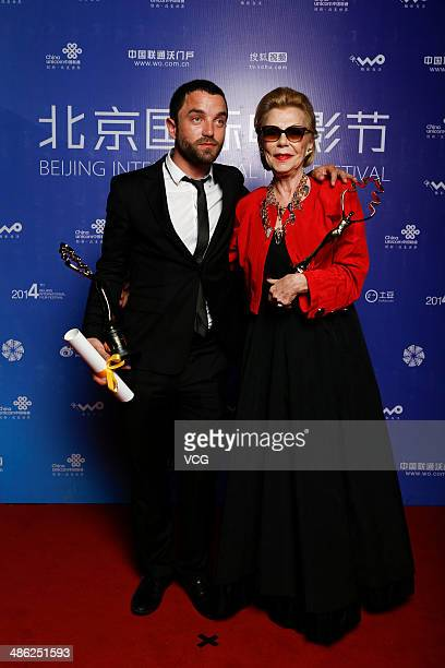 Producer Claudie Ossard and actor Guillaume Gouix pose with their trophies at the closing ceremony during 2014 Beijing International Film Festival at...