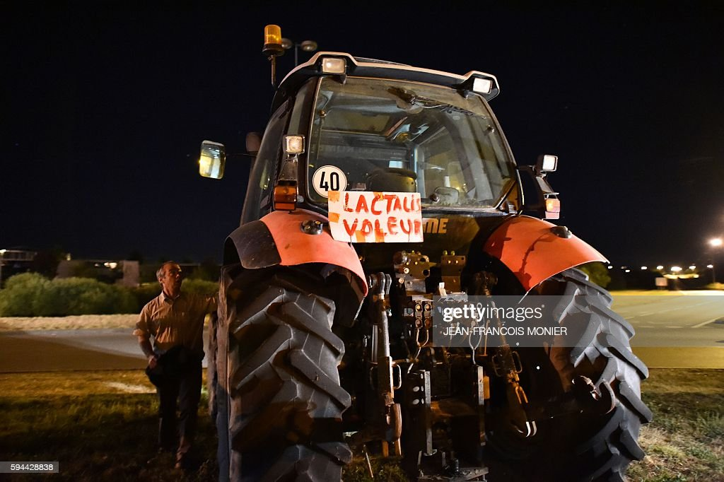 A producer comes to take his shift on the dam with a tractor on which is written 'Lactalis Thief' outside the Lactalis group headquarters in Change...