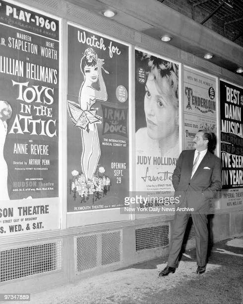 Producer David Merrick in Shubert Alley looks over poster plugging one of many shows he'll have on Broadway this season