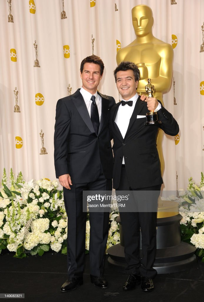 Producer for 'The Artist' Thomas Langmann poses with actor Tom Cruise in the press room at the 84th Annual Academy Awards held at the Hollywood...