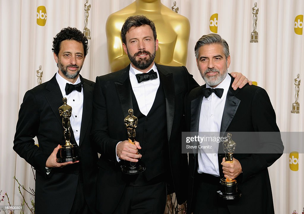Producer Grant Heslov actor/producer Ben Affleck and actor/producer George Clooney pose in the press room during the Oscars at the Loews Hollywood...
