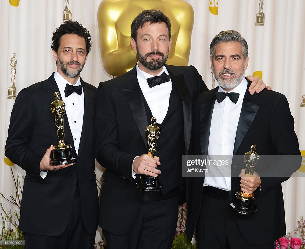 Producer Grant Heslov actor/producer Ben Affleck and actor/producer George Clooney pose in the press room during the Oscars at Loews Hollywood Hotel...
