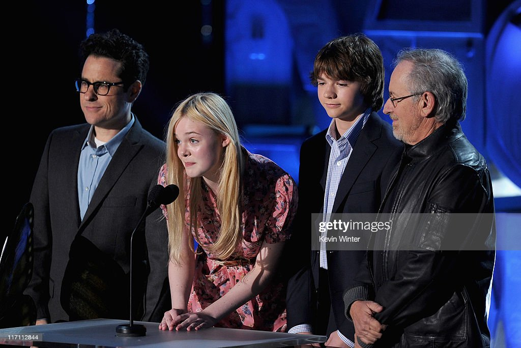 Producer <a gi-track='captionPersonalityLinkClicked' href=/galleries/search?phrase=J.J.+Abrams&family=editorial&specificpeople=253632 ng-click='$event.stopPropagation()'>J.J. Abrams</a>, actors <a gi-track='captionPersonalityLinkClicked' href=/galleries/search?phrase=Elle+Fanning&family=editorial&specificpeople=2189940 ng-click='$event.stopPropagation()'>Elle Fanning</a>, <a gi-track='captionPersonalityLinkClicked' href=/galleries/search?phrase=Joel+Courtney&family=editorial&specificpeople=7802064 ng-click='$event.stopPropagation()'>Joel Courtney</a>, and producer <a gi-track='captionPersonalityLinkClicked' href=/galleries/search?phrase=Steven+Spielberg&family=editorial&specificpeople=202022 ng-click='$event.stopPropagation()'>Steven Spielberg</a> speak onstage during the 2011 MTV Movie Awards at Universal Studios' Gibson Amphitheatre on June 5, 2011 in Universal City, California.
