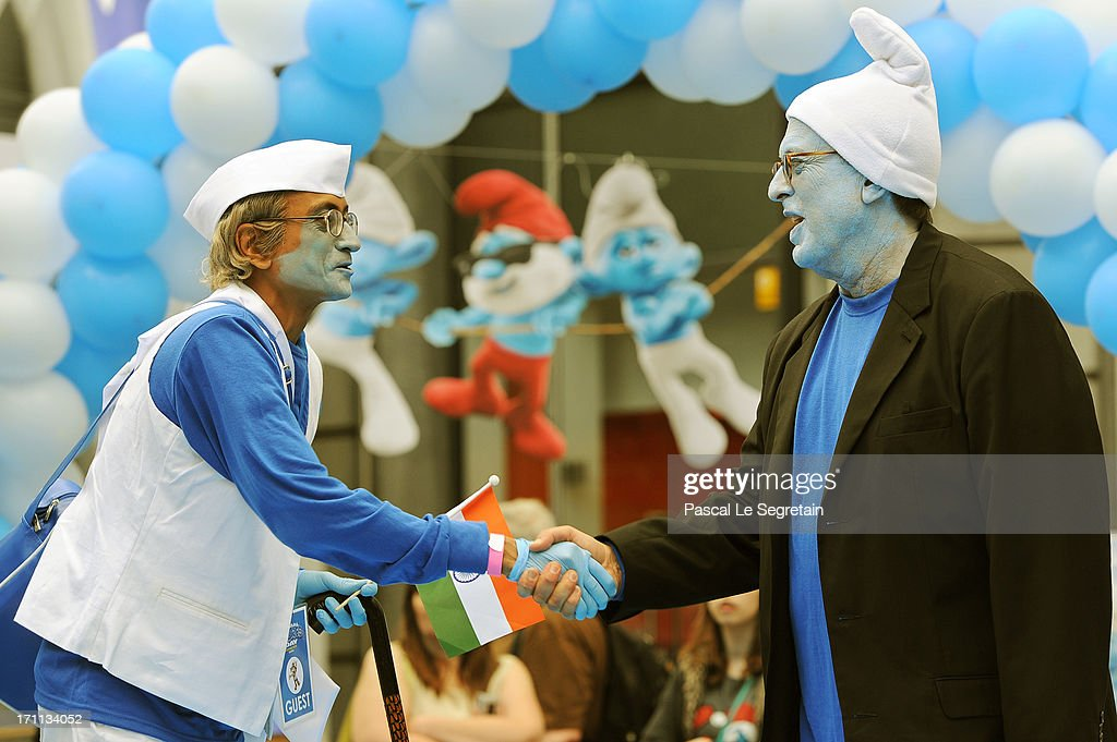 Producer Jordan Kerner (R) shakes hand with a Smurf Ambassador during a ceremony as part as Global Smurfs Day celebrations on June 22, 2013 in Brussels, Belgium.