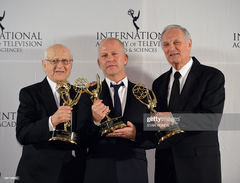 Producer Norman Lear (L) and actor Alan Alda (R) pose with their 40th Anniversary Special Founders Award with presenter Ryan Murphy (C) at the 40th International Emmy Awards November 19, 2012 in New York. AFP PHOTO/Stan HONDA