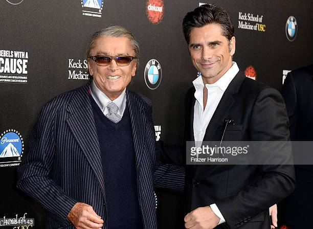 Producer Robert Evans and actor John Stamos arrive at the 2nd Annual Rebels With A Cause Gala at Paramount Studios on March 20 2014 in Hollywood...