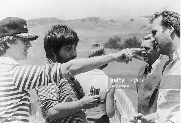 Producer Steven Spielberg points as director Tobe Hooper actors James Karen and Craig T Nelson listen on the set of the film 'Poltergeist' 1982