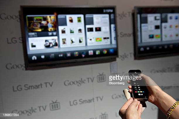 A product demonstrator uses a remote control to navigate a menu on a LG Smart TV with Google TV at the 2012 International Consumer Electronics Show...