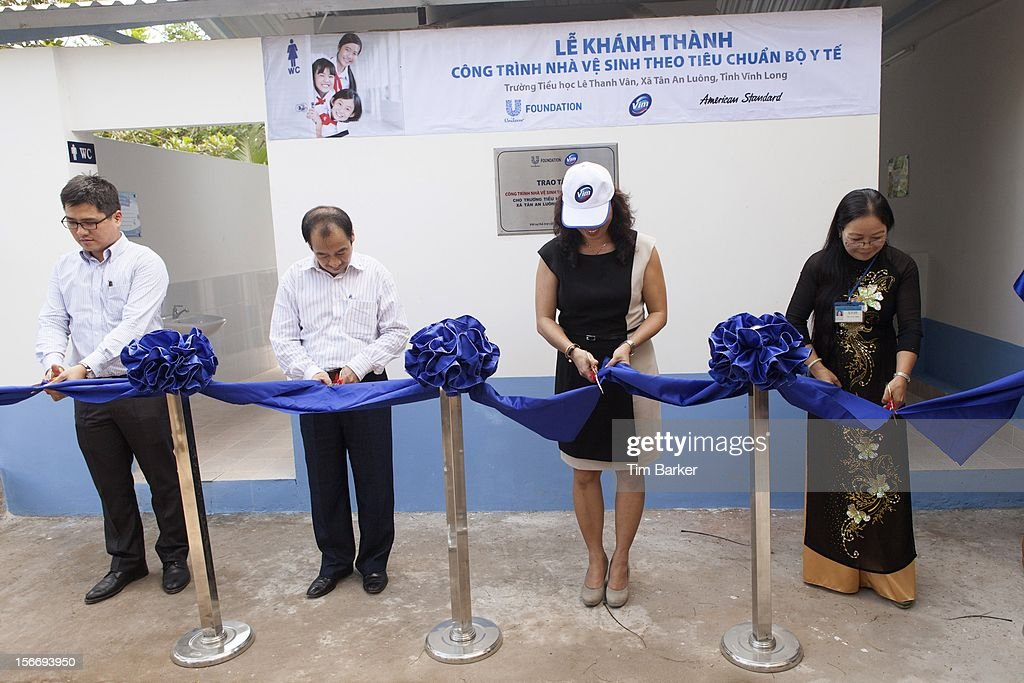 Product Manager of American Standard Hoang Ngoc Minh, Deputy Director of Environmental Management Department at the Vietnam Ministry of Health Tran Dac Phu, Marketing Vice President of Unilever Vietnam Nguyen Thi Bich Van and Principal of Le Thanh Van Primary School Ha Thi Dung cut a ribbon at the Inauguration of the new toilet complex at the Le Thanh Van Primary School on World Toilet Day on November 19, 2012 in Vinh Long, Vietnam.
