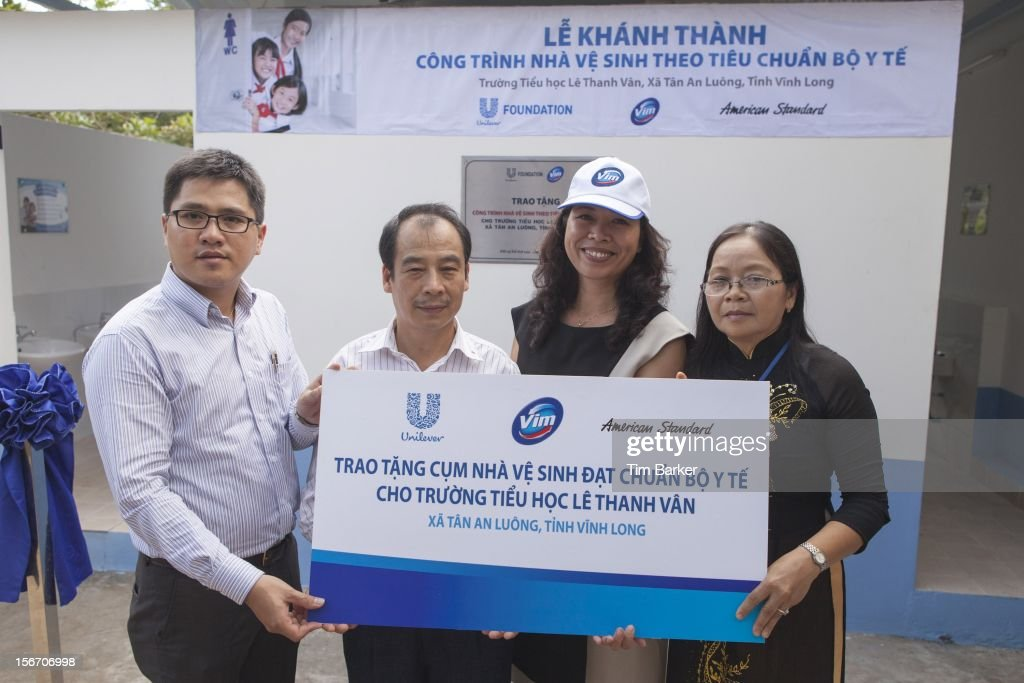 Product Manager of American Standard Hoang Ngoc Minh, Deputy Director of Environmental Management Department at the Vietnam Ministry of Health Tran Dac Phu, Marketing Vice President of Unilever Vietnam Nguyen Thi Bich Van and Principal of Le Thanh Van Primary School Ha Thi Dung hold a cheque at the inauguration of the new toilet complex at the Le Thanh Van Primary School on World Toilet Day on November 19, 2012 in Vinh Long, Vietnam.