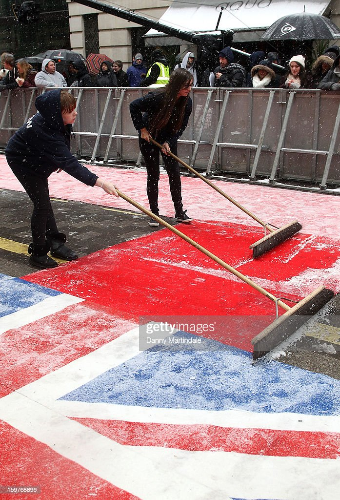 Production assistant clears snow from the red carpet during arrivals for the London judges auditions for 'Britain's Got Talent' at London Palladium on January 20, 2013 in London, England.