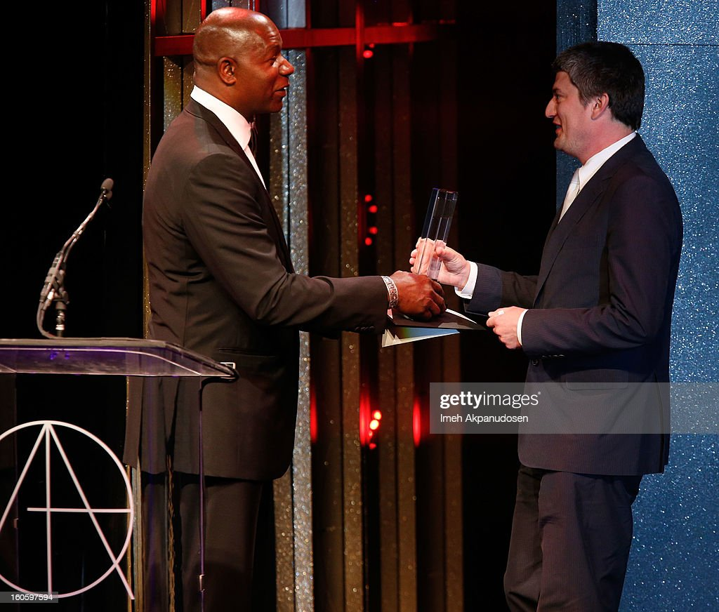Production Designer Christopher Glass (R) receives the award for Excellence in Production Design for a Commercial or Music Video 2012 - X-BOX 'Halo 4 Commissioning' onstage at the 17th Annual Art Directors Guild Awards, held at The Beverly Hilton Hotel on February 2, 2013 in Beverly Hills, California.