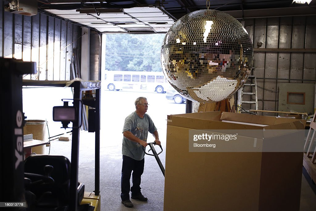 Production manager Ernie Miller positions a shipping box underneath a four foot disco ball at the Omega National Products manufacturing facility in Louisville, Kentucky, U.S., on Tuesday, Sept. 10, 2013. The U.S. Federal Reserve is scheduled to release industrial production figures on Sept. 16. Photographer: Luke Sharrett/Bloomberg via Getty Images