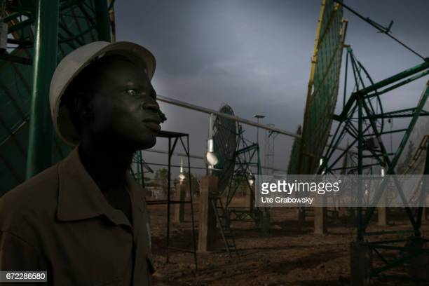 Production of solar energy through concave mirrors A worker is posing at a solar plant The energy gained supplies electricity to a rice processing...