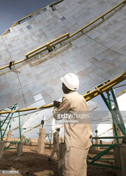 Production of solar energy through concave mirrors A worker is testing the solar system The energy gained supplies electricity to a rice processing...