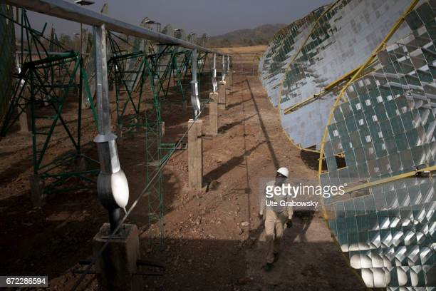 Production of solar energy through concave mirrors A worker is testing the solar system in the evening The energy gained supplies electricity to a...