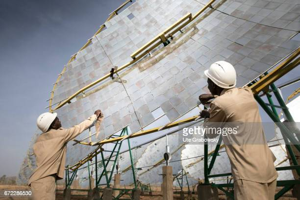 Production of solar energy through concave mirrors Two workers are testing the solar system The energy gained supplies electricity to a rice...