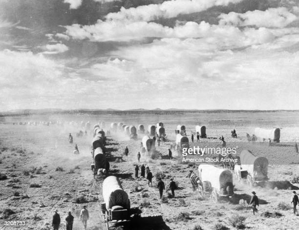 A wagon train of American homesteaders moves across the open plains migrating to the west