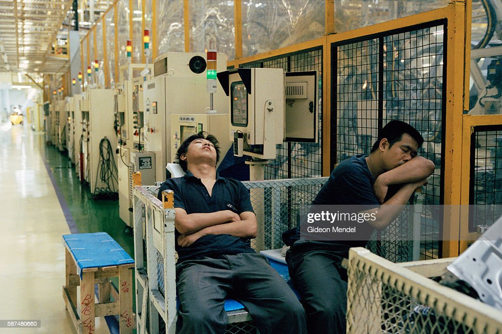 Productionline operators nap during a short break at the Hyundai factory in Beijing Hyundai is a South Korean company This Beijing factory is a joint...