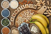Products containing magnesium: bananas, pumpkin seeds, blue poppy seed, cashew nuts, beans, almonds, sunflower seeds, oatmeal, buckwheat, peanuts, pistachios, dark chocolate and sesame seeds on wooden