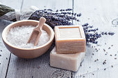Natural soap, lavender, salt on a wooden board, hygiene items for bath and spa.