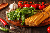 Products for cooking - pasta, tomatoes, garlic, pepper, and basil on the old wooden background.