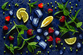 Mint, strawberry, lemon and ice for strawberry mojito on a dark background, top view