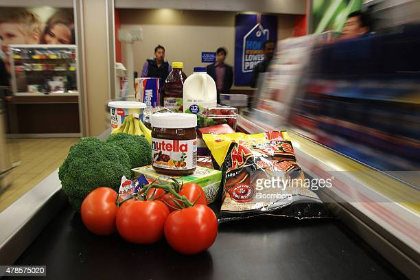 Products sit on a conveyor at the checkout counter of an Aldi Stores Ltd food store in Sydney Australia on Thursday June 25 2015 Australia's biggest...