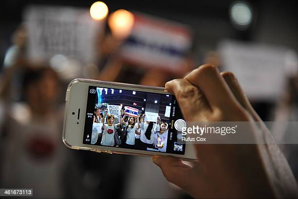 A proelection activist uses a smartphone to capture a city centre rally on January 10 2014 in Bangkok Thailand Over a thousand proelection activists...