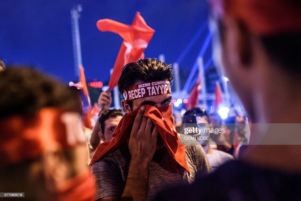 Pro-Erdogan supporter drys his eye with a piece of fabric during a rally at Taksim square in Istanbul on July 18, 2016 following the military failed coup attempt of July 15. Turkish security forces on July 18 carried out new raids against suspected plotters of the botched coup against the rule of President Recep Tayyip Erdogan, as international concern grew over the scale of the crackdown. Thousands of pro-Erdogan supporters waving Turkish flags filled the main Kizilay Square in Ankara while similar scenes were seen in Taksim Square in Istanbul, AFP photographers said. / AFP / OZAN