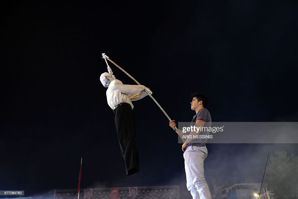 Pro-Erdogan supporter holds an effigy of US based cleric Fetullah Gulen hanged by a noosed on during a rally at Taksim square in Istanbul on July 18, 2016. The US-based cleric was accused by Ankara of orchestrating Friday's military coup attempt but he firmly denied involvement, also condemning the action 'in the strongest terms'. / AFP / ARIS