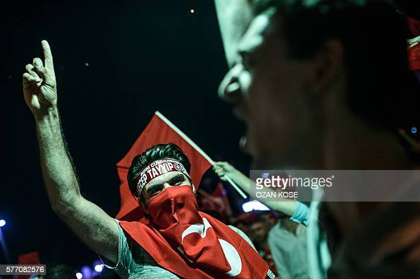TOPSHOT ProErdogan supporters chant slogans and gesture as they gather for a rally at Taksim square in Istanbul on July 18 2016 following the...