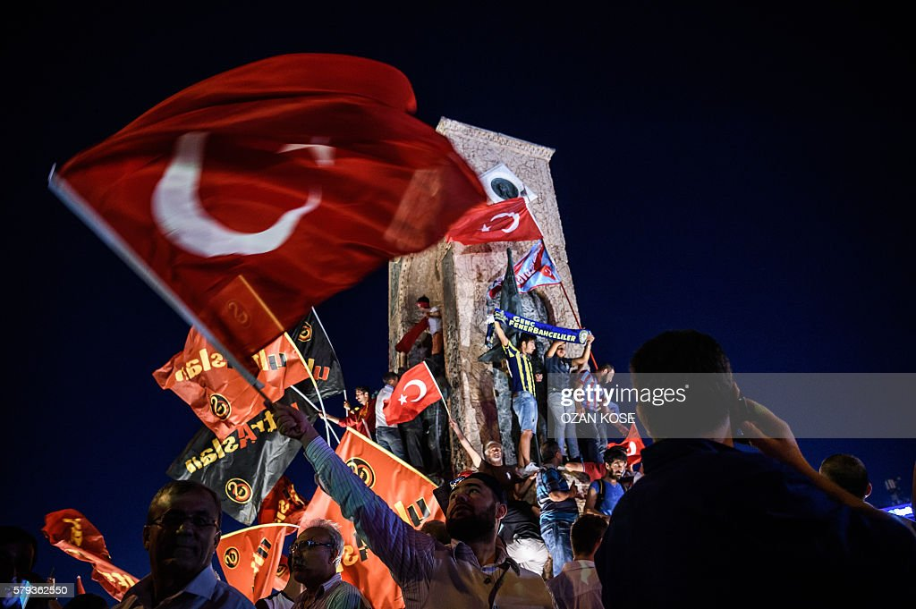 TOPSHOT - Pro-Erdogan supporters wave Turkish national flags during a rally against the military coup on Taksim square in Istanbul on July 23, 2016. Turkey pushed on with a sweeping crackdown against suspected plotters of its failed coup, defiantly telling EU critics it had no choice but to root out hidden enemies. Using new emergency powers, President Recep Tayyip Erdogan's cabinet decreed that police could now hold suspects for one month without charge, and also announced it would shut down over 1,000 private schools it deems subversive. / AFP / OZAN