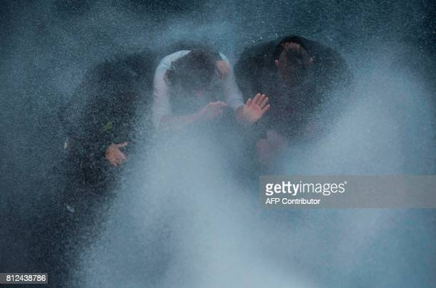 Proesters sitting on a street are sprayed with water during the 'Welcome to Hell' rally against the G20 summit in Hamburg northern Germany on July 6...