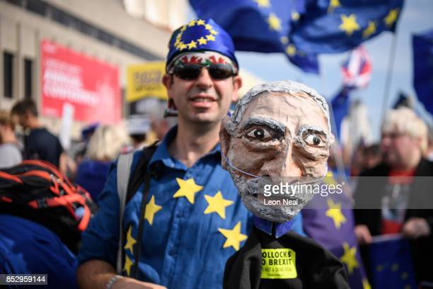 A proEU demonstrator carries a Jeremy Corbyn puppet during a march outside the main venue on the first day of the Labour Party conference on...