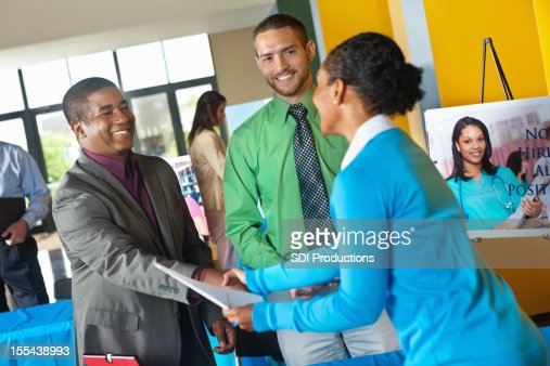 Professional accepting resume application from businesswoman at job fair